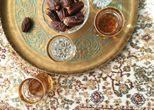 Arabic Dates and tea. Arabic food and drink. A tray filled with bowl of sweet dates and black tea Royalty Free Stock Photo