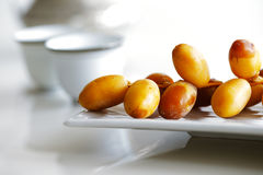 Arabic dates on a white plate with Arabic coffee cups stock photo