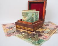 Arabic dirhams in the old wooden box. UAE dirham currency notes and coins royalty free stock photography