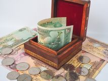 Arabic dirhams in the old wooden box. UAE dirham currency notes and coins royalty free stock image