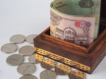 Arabic dirhams in the old wooden box. UAE dirham currency notes and coins stock photo