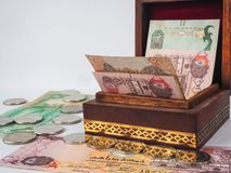 Arabic dirhams in the old wooden box. UAE dirham currency notes and coins stock images