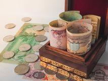 Arabic dirhams in the old wooden box. UAE dirham currency notes and coins stock photography