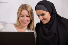 Arabic and european women watching Stock Image