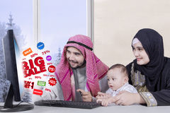Arabic family with BIG SALE. Portrait of happy muslim family using computer and looking big sale on monitor while sitting in living room with winter background royalty free stock image