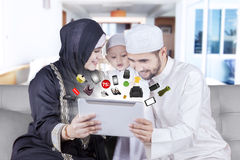 Arabic family buying products online. Happy middle eastern family using a digital tablet for shopping products online at home stock images
