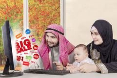 Arabic family with computer at home. Arabic family using computer for shopping online while sitting in the living room with autumn background on the window royalty free stock images