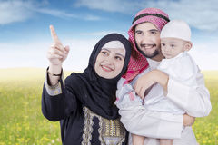 Arabic family looking at something at field. Portrait of happy middle eastern family standing on the meadow while looking at something on the sky Stock Image