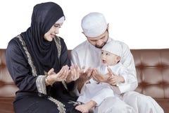 Arabic family praying together on sofa Stock Image