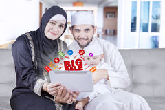 Arabic family with promo online on tablet. Happy middle eastern family holding a digital tablet with promo online, shot at home stock photography