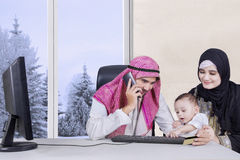 Arabic family sitting at living room. Portrait of happy muslim family sitting in the living room while father talking by phone and holding card credit with royalty free stock image