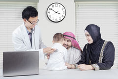 Arabic family at the specialist doctor. Middle eastern family visiting the specialist doctor in the hospital and checking their child health Stock Image