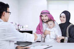 Arabic father shaking hands with doctor Royalty Free Stock Photos