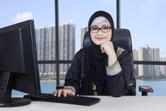 Arabic female entrepreneur works in office. Arabic young businesswoman smiling at the camera while working with computer in the office Royalty Free Stock Photography