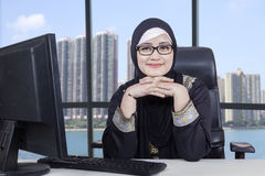 Arabic female worker with computer in office. Confident Arabic female entrepreneur sitting in the office with computer on desk and smiling at the camera royalty free stock photo