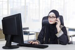 Arabic female worker works in office. Arabic female entrepreneur talking on the mobile phone while working with a computer in the office royalty free stock photos