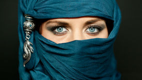 Arabic girl glance. Portrait of an arabic young woman with her beautiful blue eyes in traditional islamic cloth niqab Stock Photos