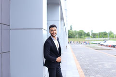 Arabic guy in business center stands smiling walking slow Royalty Free Stock Photo