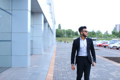 Arabic guy in business center stands smiling walking slow Royalty Free Stock Images