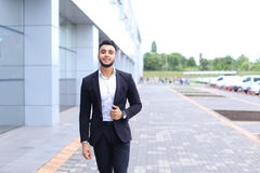 Arabic guy in business center stands smiling walking slow Royalty Free Stock Image