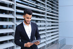 Arabic guy in business center stands smiling Royalty Free Stock Image