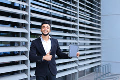 Arabic guy in business center stands smiling Royalty Free Stock Photo