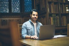 Arabic man working in library with computer. Education smart mood. Arabic handsome man working in library with computer. Education smart mood stock photo