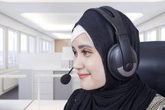 Arabic helpline operator using headset. Portrait of beautiful Arabic helpline operator using headset to work in the office room Stock Photo