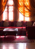Arabic interior - coffee tables and orange curtains Royalty Free Stock Images