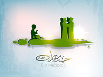 Arabic Islamic calligraphic text Eid Mubarak with silhouettes of Royalty Free Stock Images