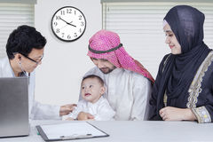 Arabic little boy looking at the doctor. Portrait of Arabic cute little boy visiting a doctor with his parents and looking at the doctor Royalty Free Stock Photography