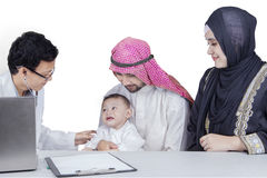 Arabic male child and his family visit doctor. Picture of Arabic male child and his parents visiting a doctor, isolated on white background stock image