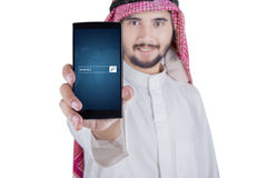 Arabic man displaying www text on cellphone. Young Arabic person displaying a smartphone with www text on the screen, isolated on white background Royalty Free Stock Image