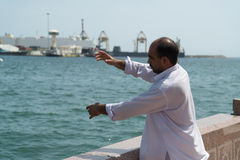 Arabic man fishing in harbor Royalty Free Stock Photography