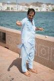 Arabic man fishing in harbor. MUSCAT, OMAN, 14 JUNE 2014: Arabic man fishing in harbor stock photo