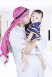 Arabic man kissing his child. Portrait of arabic men with muslim clothes while standing and kissing his child at home royalty free stock image