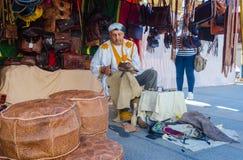 Arabic man making shoes in a market. Badajoz, Spain - September 23, 2016: Arabic man making shoes in a market during celebration of Almossassa, Badajoz Stock Image