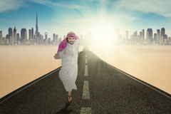 Arabic man running on the highway. Photo of Arabic businessman running on the highway while wearing islamic clothes Stock Photography