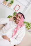 Arabic Man With Smartphone. Middle Eastern Man Having Phone Conversation On Sofa Royalty Free Stock Image