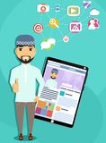 Arabic man with tablet computer. The concept of social networking. Arabic man with tablet computer showing a social network. Personal page of a social network Stock Image