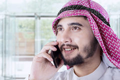 Arabic man talking on cellphone in office lobby Stock Image