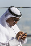 Arabic man tapping on his iphone Royalty Free Stock Photography