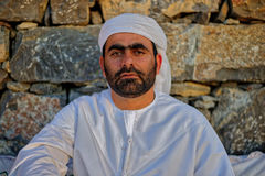 Arabic man in traditional dress. Portrait of Arabic man wearing traditional dress leaning against stone wall Stock Images