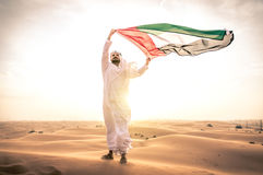Arabic man with traditional emirates clothes. Walking in the desert with his falcon bird royalty free stock images