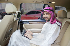 Arabic man working in car and smiling Royalty Free Stock Images