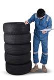 Arabic mechanic checks the texture of tires. Image of Arabic mechanic wearing uniform and checking the texture of tires, isolated on white background Stock Image