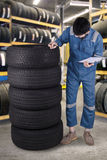 Arabic mechanic checks the tires in workshop. Middle eastern mechanic working in the workshop while wearing uniform and checking a pile of tires Royalty Free Stock Photo