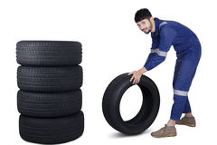 Arabic mechanic pushing a tire. Portrait of Arabic mechanic smiling at the camera while pushing a tire with a pile of tires in the studio Stock Image