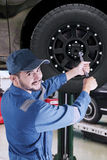 Arabic mechanic replacing a car wheel. Portrait of Arabic mechanic working in the workshop and replace a car wheel Royalty Free Stock Photos