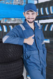 Arabic mechanic with tires shows thumb up Royalty Free Stock Image